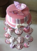 Striped top tier with handmade sugar butterfly above a selection of domed cupcakes and temari