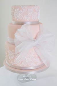 Three tier nude coated cake overlaid with handpiped lace, finished with a large bow (all inspired by dress design)